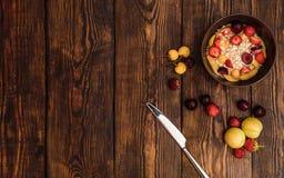 Mesa de desayuno con las gachas de avena, las frutas maduras y las bayas foto de archivo