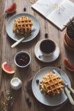 Mesa de desayuno con las galletas, el café, el atasco, las frutas y el libro para leer Imágenes de archivo libres de regalías