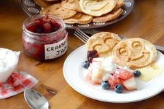 Mesa de desayuno: crepes, ensalada de fruta, atasco, yogur Foto de archivo