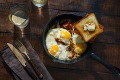 Mesa de desayuno Huevos fritos con tocino en sartén Foto de archivo libre de regalías