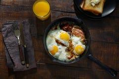 Mesa de desayuno llena Huevos fritos con tocino en sartén Imagenes de archivo