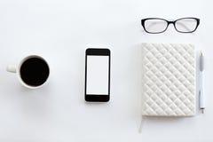 Mesa de escritório branca com vidros, telefone celular, café e pena Imagem de Stock
