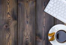 Mesa de escritório com espaço da cópia Dispositivos teclado e rato sem fio de Digitas na tabela de madeira escura com xícara de c Foto de Stock Royalty Free