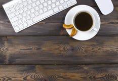 Mesa de escritório com espaço da cópia Dispositivos teclado e rato sem fio de Digitas na tabela de madeira escura com xícara de c Imagem de Stock Royalty Free