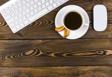 Mesa de escritório com espaço da cópia Dispositivos teclado e rato sem fio de Digitas na tabela de madeira escura com xícara de c Imagens de Stock