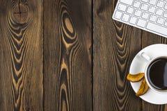 Mesa de escritório com espaço da cópia Dispositivos teclado e rato sem fio de Digitas na tabela de madeira escura com xícara de c Fotografia de Stock Royalty Free