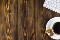 Mesa de escritório com espaço da cópia Dispositivos teclado e rato sem fio de Digitas na tabela de madeira queimada com xícara de Fotos de Stock Royalty Free