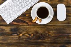 Mesa de escritório com espaço da cópia Dispositivos teclado e rato sem fio de Digitas na tabela de madeira queimada com xícara de Foto de Stock
