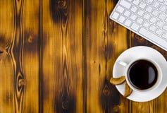 Mesa de escritório com espaço da cópia Dispositivos teclado e rato sem fio de Digitas na tabela de madeira queimada com xícara de Imagem de Stock