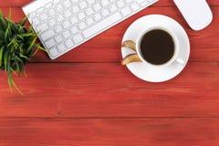 Mesa de escritório com espaço da cópia Dispositivos teclado e rato sem fio de Digitas na tabela de madeira vermelha com o copo do Foto de Stock