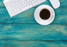 Mesa de escritório com espaço da cópia Dispositivos teclado e rato sem fio de Digitas na tabela de madeira vermelha com xícara de Imagem de Stock Royalty Free