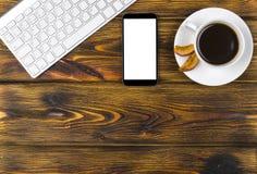 Mesa de escritório com espaço da cópia Dispositivos teclado, rato e smartphone sem fio de Digitas com a tela vazia na tabela de m Fotos de Stock Royalty Free