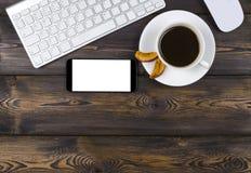 Mesa de escritório com espaço da cópia Dispositivos teclado, rato e smartphone sem fio de Digitas com a tela vazia na tabela de m Imagem de Stock Royalty Free
