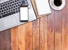 Mesa de escritório com portátil e o telefone esperto fotos de stock royalty free