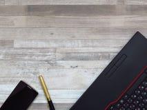 Mesa de escritório com portátil preto, telefone celular dourado da cor, pena luxuoso dourada no fundo de madeira branco da textur foto de stock