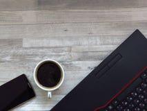 Mesa de escritório com portátil preto, telefone celular dourado da cor, uma xícara de café Negócios Sucesso Ruptura de café Traba fotografia de stock