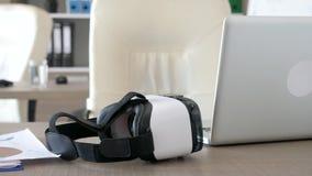 Mesa de escritório com uns auriculares da realidade virtual de VR que encontram-se neles vídeos de arquivo