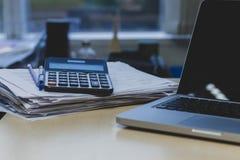 Mesa de escritório um relatórios de papel da pilha e portátil do computador foto de stock