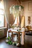 Mesa de jantar com cadeiras, o candelabro da flor, frutos e as plantas carnudas clássicos no espaço do sótão com flores fotos de stock royalty free