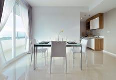 A mesa de jantar com tabela ajustou-se no interi vivo moderno luxuoso branco Fotos de Stock Royalty Free