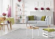 Mesa de jantar com toalha de mesa verde na sala de visitas escandinava brilhante com mobília branca e de madeira, sofá cinzento e fotografia de stock