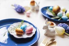 mesa de jantar festiva do feriado de easter com o ramalhete metálico dourado da cutelaria e dos ovos, do jacinto e da tulipa Fotografia de Stock