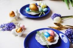mesa de jantar festiva do feriado de easter com o ramalhete metálico dourado da cutelaria e dos ovos, do jacinto e da tulipa Imagem de Stock Royalty Free