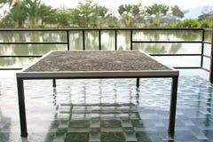 Mesa de jantar sentando no assoalho perto do lago, estilo tailandês foto de stock royalty free