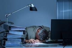 Mesa de Leaning Head On do homem de negócios por pastas ao trabalhar tarde foto de stock royalty free