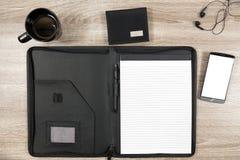 Mesa de madeira com smartphone, fones de ouvido, carteira, caneca de café e imagem de stock