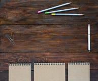 Mesa de madeira escura de Brown com blocos de desenho e lápis Fotos de Stock