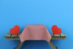 Mesa de picnic con dos corazones rojos Foto de archivo
