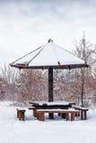 Mesa de picnic de madera con el paraguas de madera en el invierno Imagen de archivo
