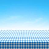 Mesa de picnic vacía cubierta con el mantel a cuadros azul Foto de archivo libre de regalías