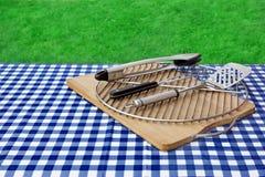 Mesa de picnic vacía, mantel a cuadros, rejilla, herramientas de la parrilla del Bbq Imagenes de archivo
