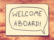 Mesa de projeto com a boa vinda da frase a bordo de escrito à mão sobre a placa de madeira fotografia de stock