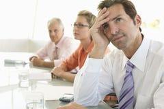 Mesa de reuniones agujereada de Looking Away At del hombre de negocios Fotografía de archivo