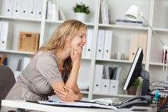 Mesa de sorriso de Using Computer At da mulher de negócios no escritório fotografia de stock royalty free
