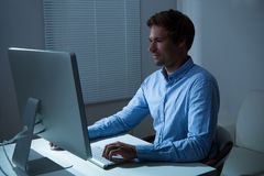 Mesa de Working Late At do homem de negócios no escritório imagens de stock royalty free