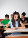 Mesa de Writing Paper At do estudante fêmea dentro fotos de stock