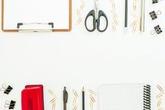 Mesa del espacio de trabajo con el tablero, el cuaderno, la pluma y los accesorios en el fondo blanco Endecha plana, visión super Imagen de archivo libre de regalías