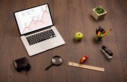 Mesa do computador com portátil e carta vermelha da seta na tela Imagem de Stock