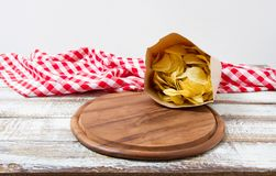 Mesa do corte, toalha de mesa enrugada quadriculado na tabela, microplaquetas de batata no bloco de papel, conceito do feriado imagem de stock royalty free