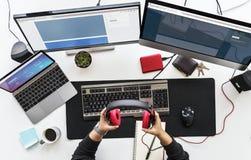 Mesa do trabalho com telas e dispositivos eletrónicos múltiplos Fotos de Stock