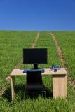 Mesa e computador no campo verde com trajeto fotografia de stock