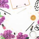 Mesa elegante con los cosméticos, los accesorios, el bijouterie y las ramas de la mujer de la lila rosada en el fondo blanco Ende Imagenes de archivo