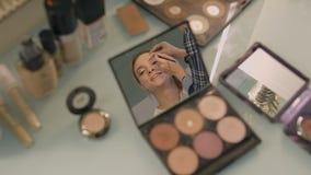 Mesa em um salão de beleza refletido no espelho de sua cara compacta da menina Estilista profissional video estoque