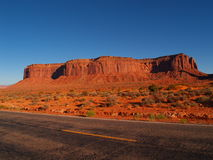 Mesa and Highway. A state highway runs past a mesa near Monument Valley Navajo Tribal Park Royalty Free Stock Photography
