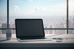 Mesa moderna con el ordenador portátil en blanco imagen de archivo