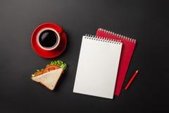 Mesa negra de la oficina con la taza roja de café, de cuaderno y de bocadillo para el almuerzo fotos de archivo libres de regalías